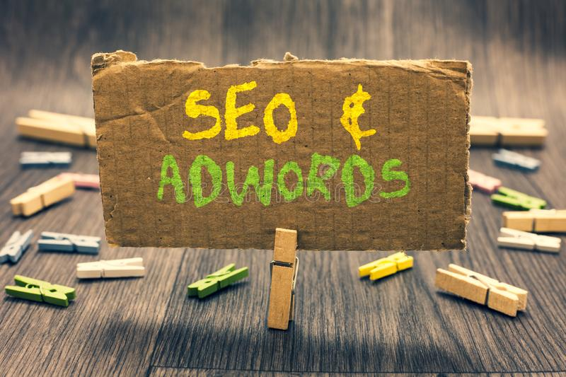 Writing note showing Seo and Adwords. Business photo showcasing Pay per click Digital marketing Google Adsense Clothespin holding. Paperboard important royalty free stock images