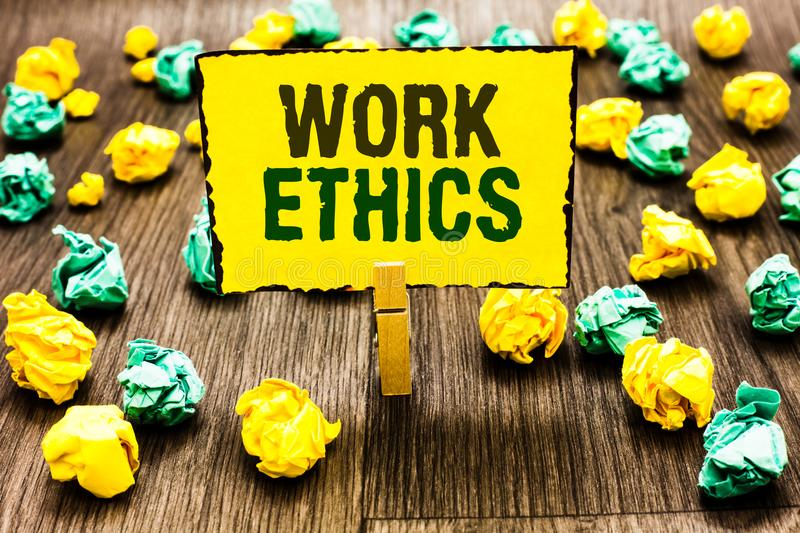 Writing note showing Work Ethics. Business photo showcasing A set of values centered on the importance of doing work Clothespin ho. Lding yellow note paper stock photography