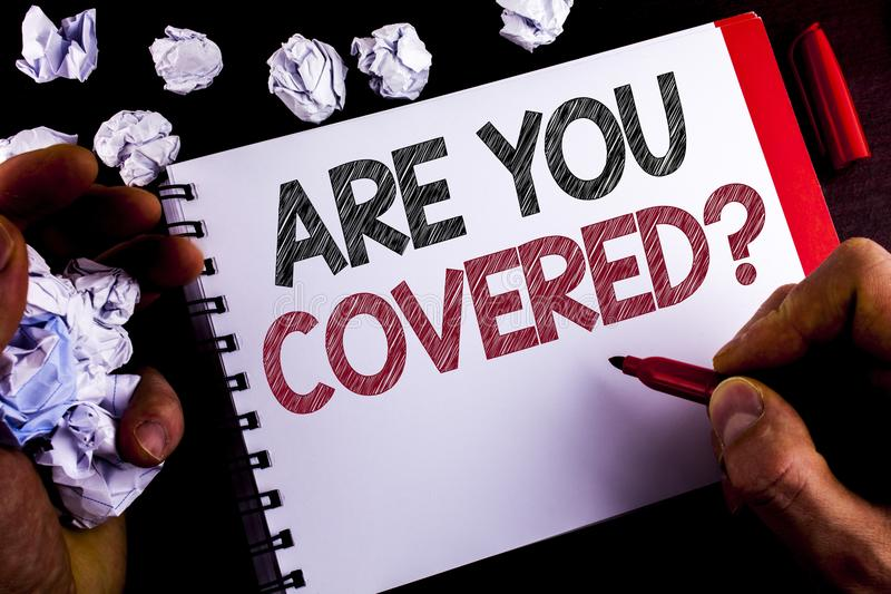 Writing note showing Are You Covered Question. Business photo showcasing Health insurance coverage disaster recovery written by M. An Notepad holding Marker stock image