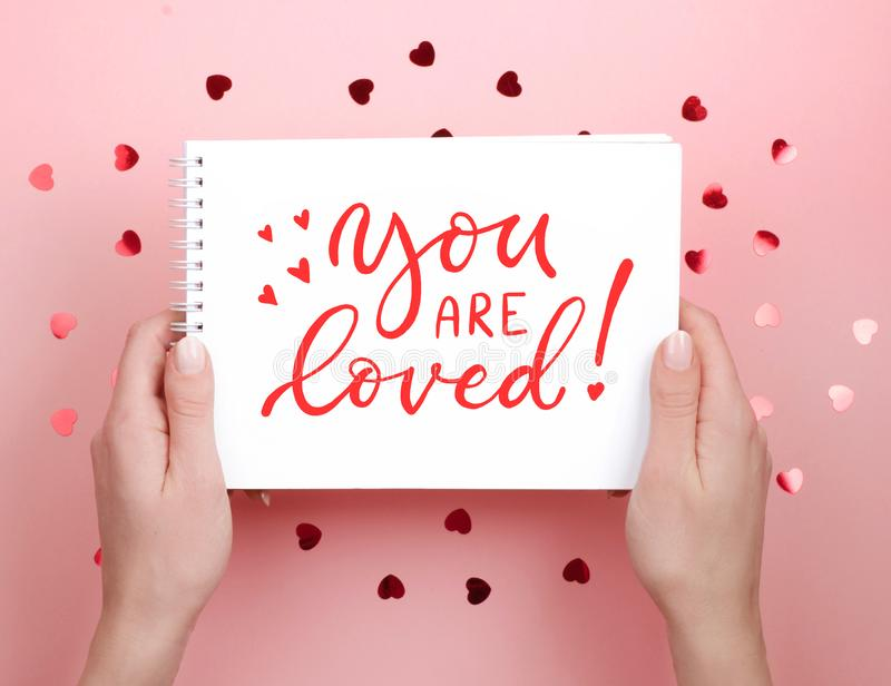 The writing on notebook. You are loved. Lettering, calligraphy royalty free stock photo