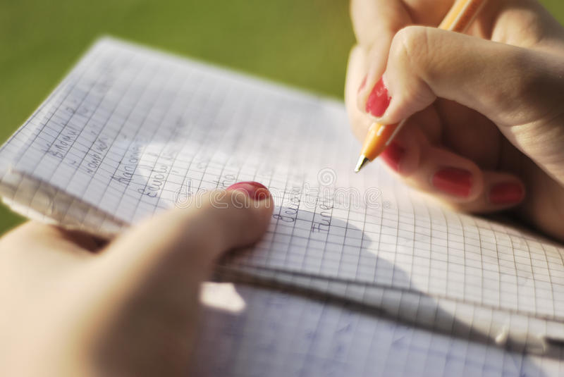 Writing in Park. A teenage girl's hand writing on a white notebook outdoors stock photo