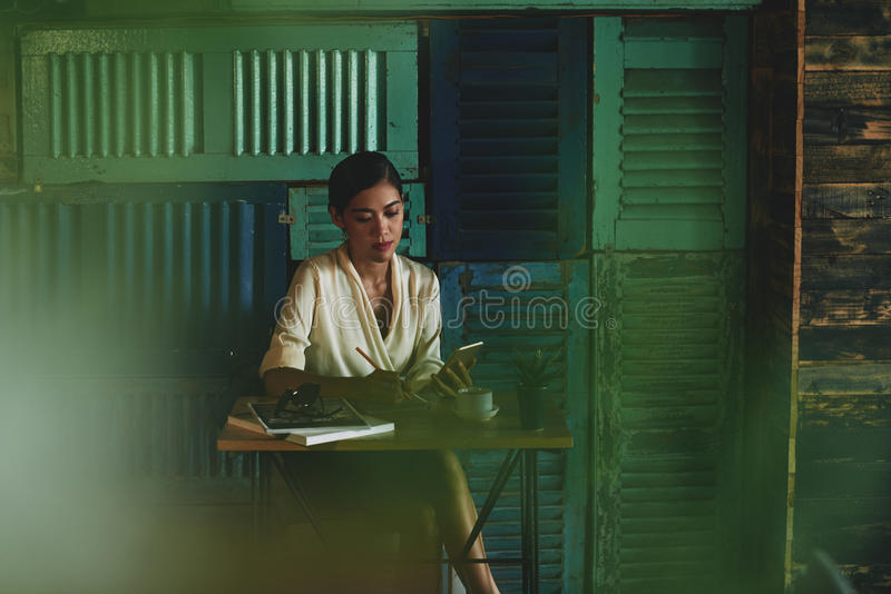 Writing plans. Gorgeous Asian woman sitting at cafe table and writing in her notepad royalty free stock photography