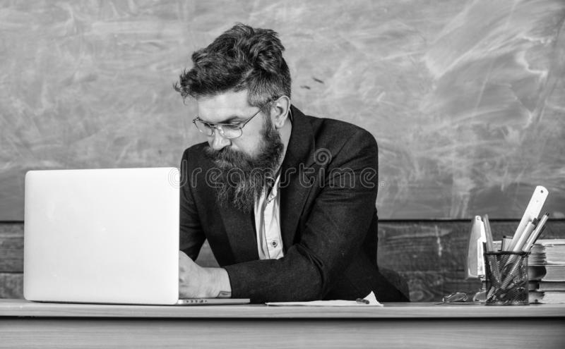 Writing school report. School teacher typing report laptop. Teacher sit at desk with laptop. Back to school concept royalty free stock photography