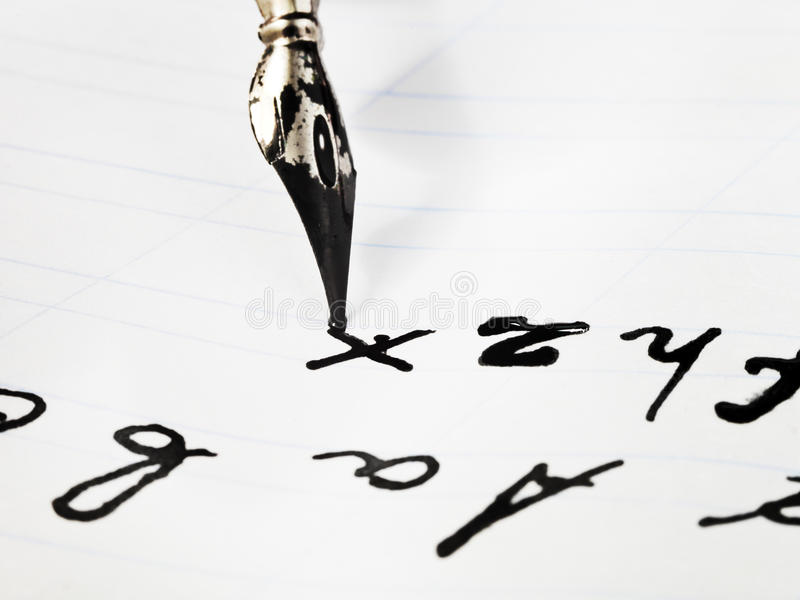 Writing of set of letters by black ink nib. On white sheet of notebook close up stock image