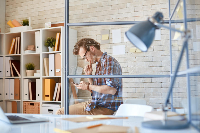 Writing sms. Pensive businessman with smartphone writing sms in office stock image