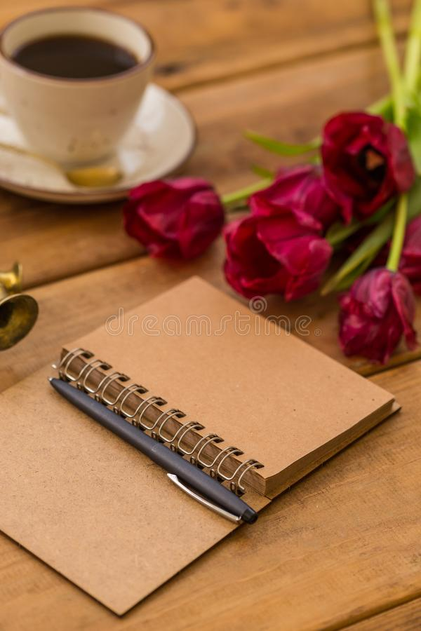 Writing in spring season. Open notepad, black pen and red-wine t. Writing in spring season. Open notepad, black pen, red-wine tulips and a cup of coffee on stock photo