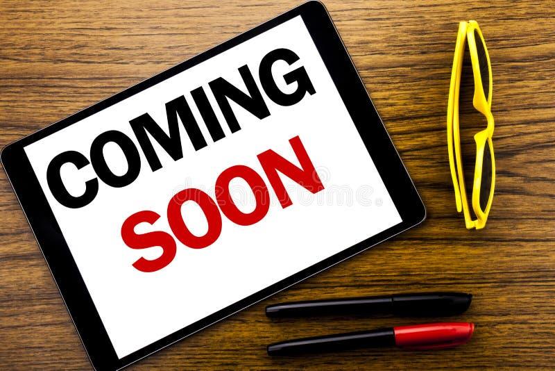 Writing tekst pokazuje Przychodzić Wkrótce Biznesowy pojęcie dla wiadomości przyszłości Pisać na pastylka laptopie, drewniany tło obraz stock