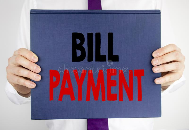 Writing text showing Bill Payment. Business concept for Billing Pay Costs written on book notebook paper holding by the man in sui. Writing text showing Bill royalty free stock image