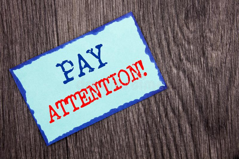 Writing text showing Pay Attention. Business photo showcasing Be Careful Beware Mindful Alarm written on Blue Sticky Note Paper o. Writing text showing Pay royalty free stock images