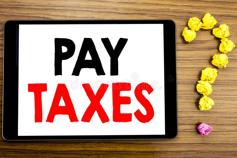 Writing text showing Pay Taxes. Business concept for Taxation Overtax Return written on tablet computer on the wooden background w. Writing text showing Pay stock photography