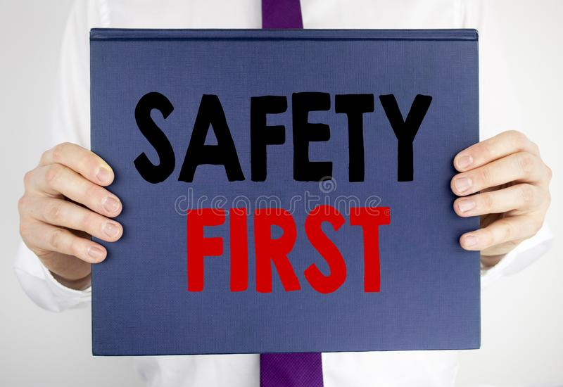 Writing text showing Safety First. Business concept for Safe Warning written on book notebook paper holding by the man in suit blu stock photo