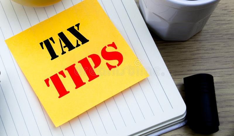 Writing text showing Tax Tips. Business concept for Taxpayer Assistance Refund Reimbursement written sticky note empty paper, Wood. Writing text showing Tax Tips royalty free stock photo