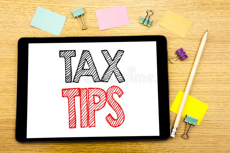 Writing text showing Tax Tips. Business concept for Tip Forn Taxes Written on tablet laptop, wooden background with sticky note an. Writing text showing Tax Tips royalty free stock image
