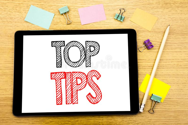 Writing text showing Top Tips. Business concept for Expert Tip Guidance Written on tablet laptop, wooden background with sticky no. Writing text showing Top Tips stock photography