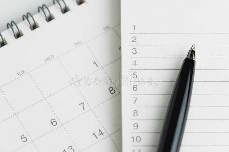 Writing to do list or work target plan concept, black pen on not. Epad with list of numbers on clean desktop flip calendar royalty free stock image
