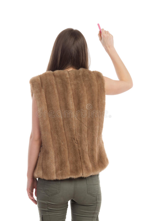 Writing Woman Rear View Isolated. Woman in brown fur waistcoat standing, holding chalk and writing. Rear view. Three quarter length studio shot isolated on white royalty free stock photos