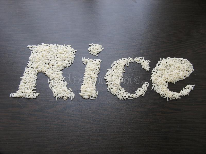 Writing the word Rice with rice seeds on a table with brown wooden backgroun. D . Italic font. Top view stock image