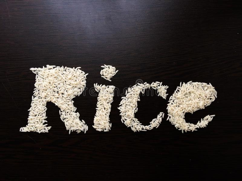 Writing the word Rice with rice seeds on a table with brown wooden background. Italic font. Top view stock photos