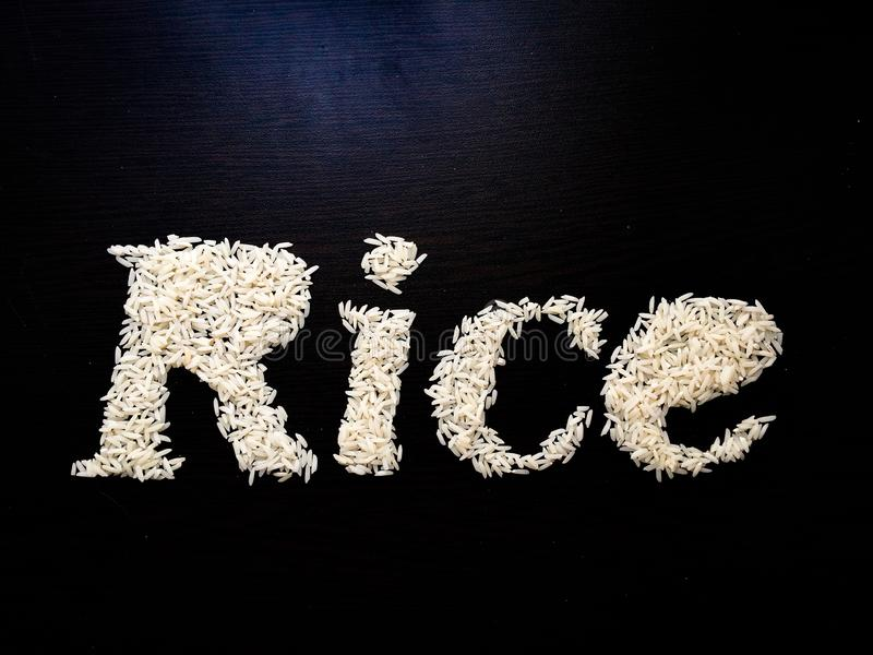 Writing the word Rice with rice seeds on a table with brown wooden background. Italic font. Top view stock images