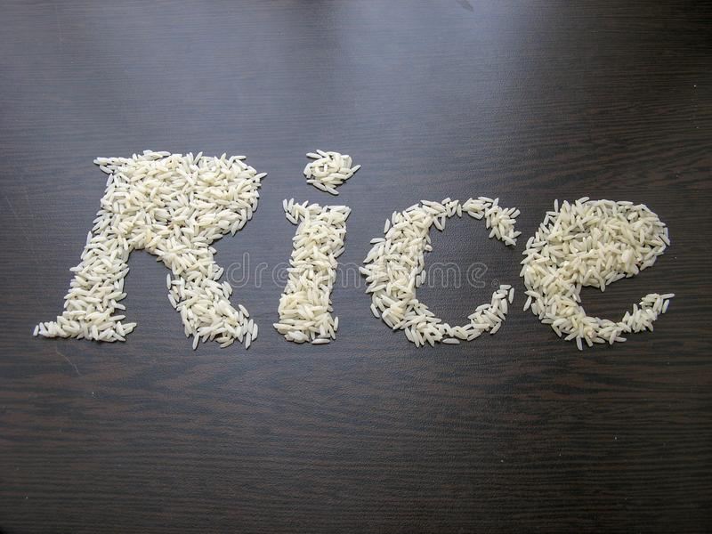 Writing the word Rice with rice seeds on a table with brown wooden background. Italic font. Top view stock image