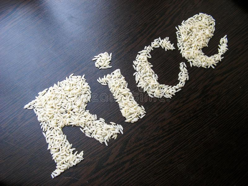 Writing the word Rice with rice seeds on a table with brown wooden background. Italic font. Top view. Crooked angle royalty free stock image