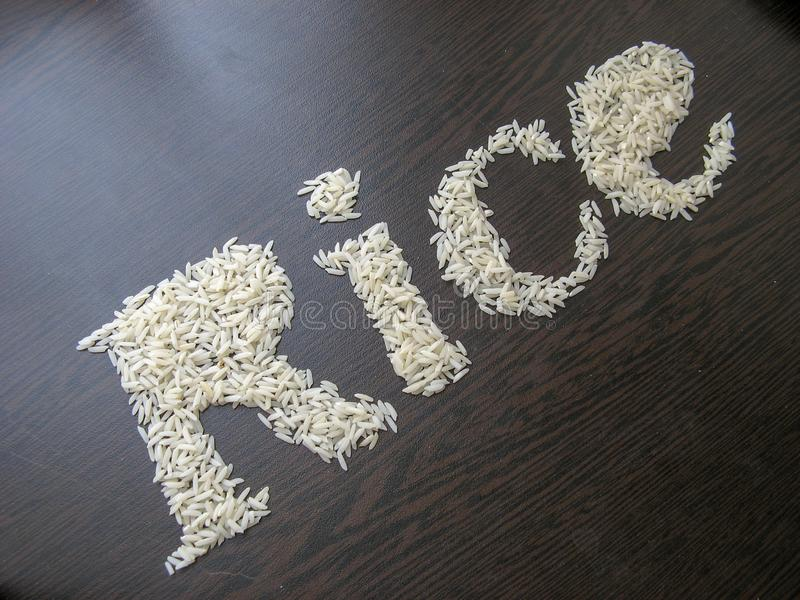 Writing the word Rice with rice seeds on a table with brown wooden background. Italic font. Top view. Crooked angle royalty free stock photography
