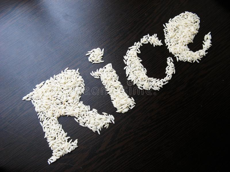 Writing the word Rice with rice seeds on a table with brown wooden background. Italic font. Top view. Crooked angle stock photos