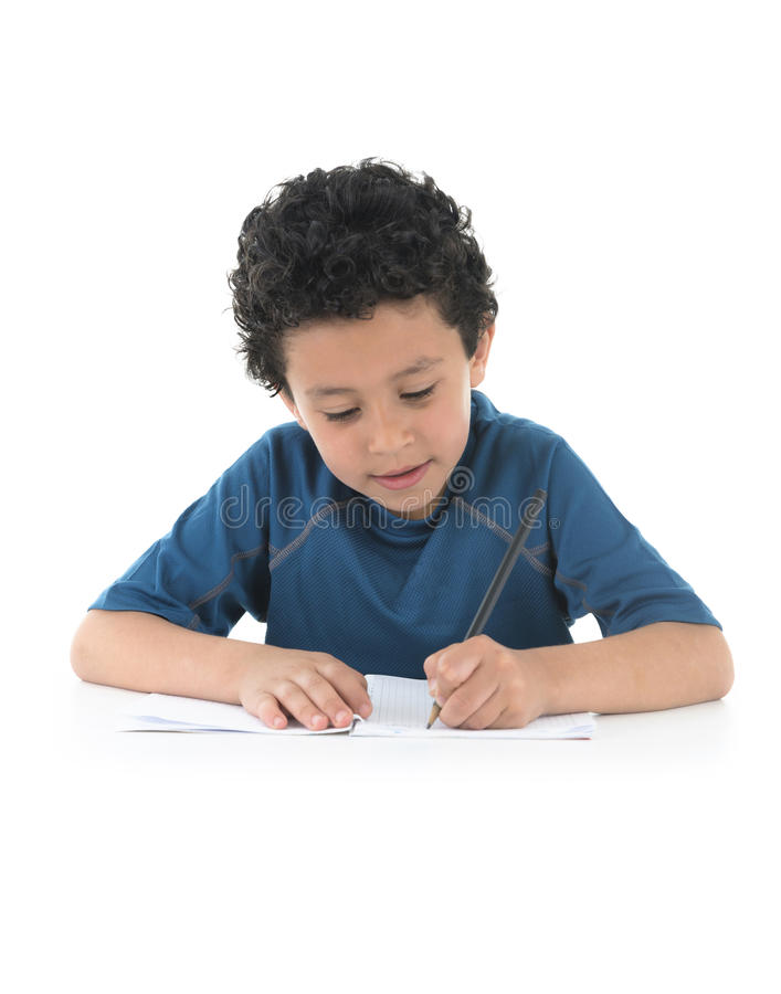 Writing. Young Boy Writing His Homework Isolated on White Background royalty free stock images