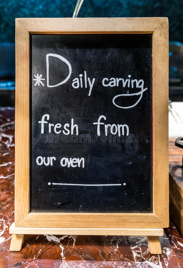 Writings on a blackboard with wooden frame that indicates the food is made fresh daily from the oven royalty free stock image