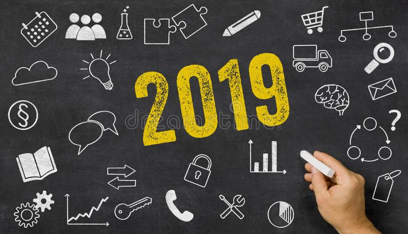 2019 written on a blackboard with icons royalty free stock image