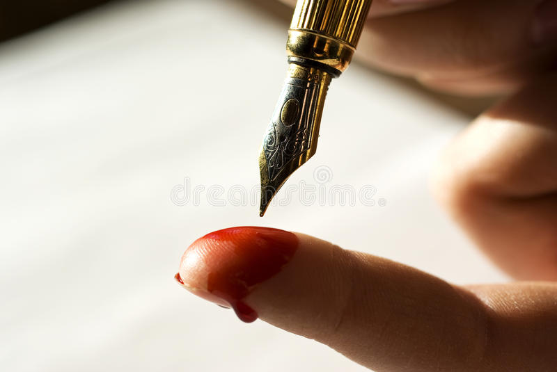 Written in blood. Concept, hand holding fountain pen over blooded finger stock photos