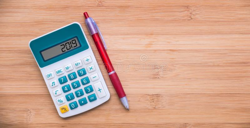 2019 written on a calculator and a pen on wood background royalty free stock photos