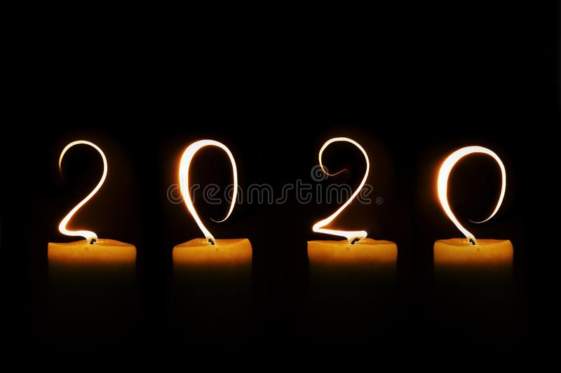 2020 written with candle flames on black background greeting card. 2020 written with candle flames on black background, greeting card stock image