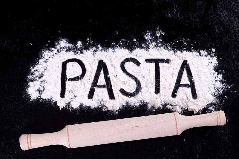 On written flour pasta. Dark background. Rolling pin. On written flour pasta. Broken egg. Spilling pasta. royalty free stock photography