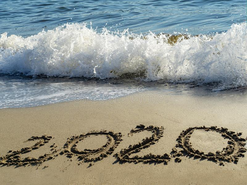 2020 written by hand on the sand beach with beautiful wave and clear blue sea. Handwritten lettering numbers 2020 on sea shore royalty free stock photography