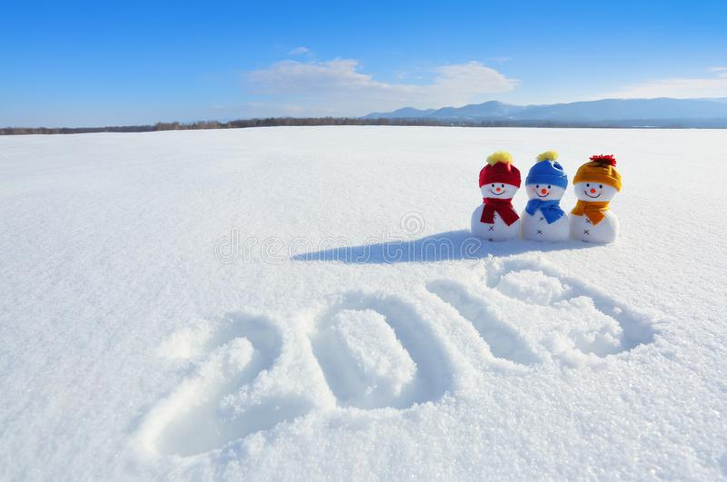 2019 written on the snow. Smiling snowman with hats and scarfs are standing on the field with snow. Landscape with mountains. royalty free stock photography