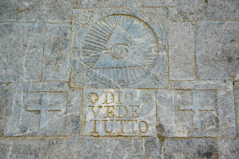 Written on the stone wall `Dio vede tutto`/`God sees everything` and masonic symbol above. Space for text royalty free stock photo