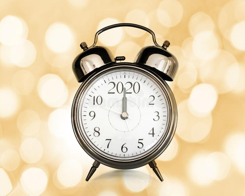 2020 written on a vintage alarm clock, bokeh lights background, happy new year eve party time and midnight countdown stock photos