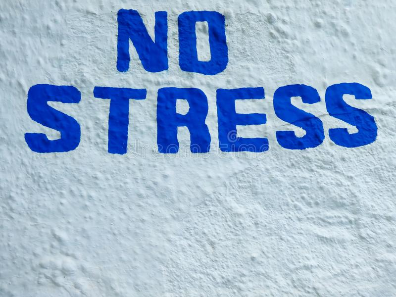 Written on a white background and a blue capital lettering NO STRESS. Detail of a blue capital lettering on a white background NO STRESS stock photo