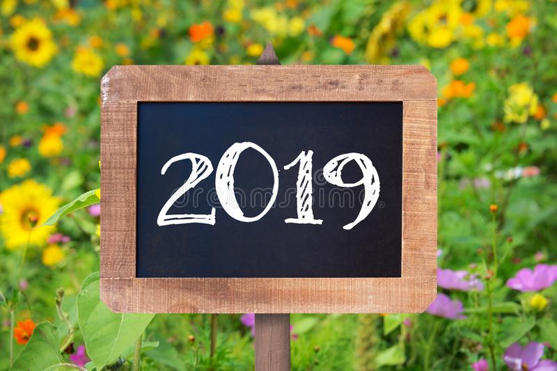 2019 written on a wooden sign, Sunflowers and wild flowers stock photo