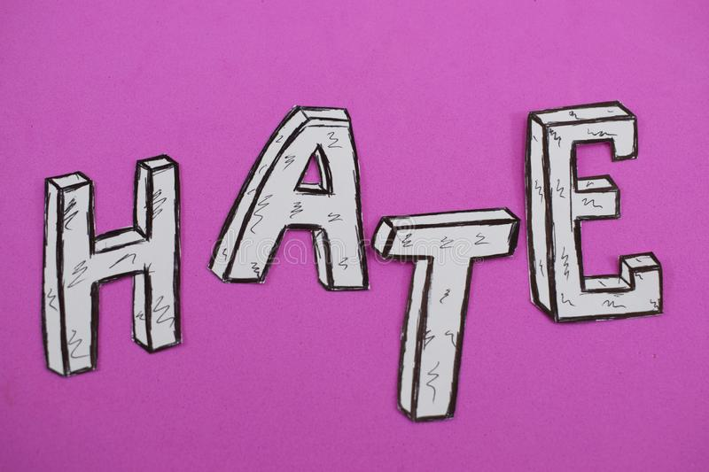 Written word hate, white on a pink background.  royalty free stock image