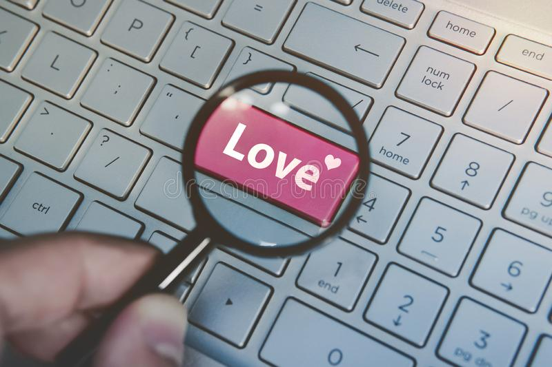 Written word love on keyboard red button viewed through the magnifying glass. Close up of male hand with loupe searching stock image