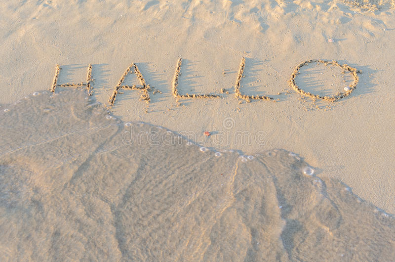 Written words Hallo on sand of beach. In sunny summer morning. Vacation holidays concept royalty free stock images
