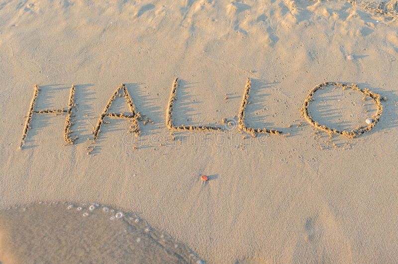 Written words Hallo on sand of beach. In sunny summer morning. Vacation holidays concept royalty free stock photography