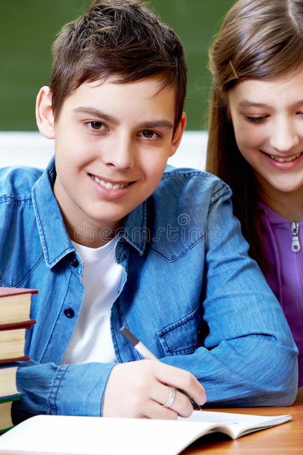 Written work. Portrait of smart guy at workplace looking at camera with his classmate near by stock photos