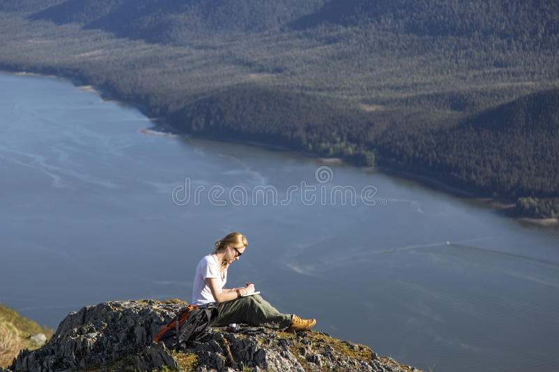 Making notes on top of the mountain royalty free stock photo