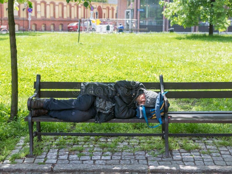 WrocÅ 'aw, Polen - Maj 24 2019: Den hemlösa mannen sover på en bänk nära ett nybyggt arkivfoton