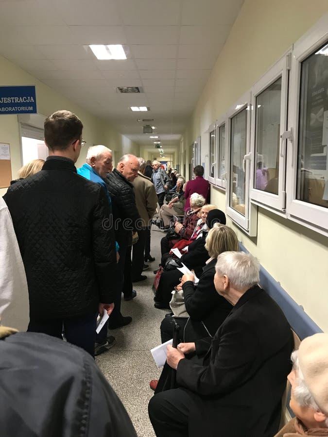 WrocÅ 'aw Polska, Maj, - 6 2019: Pacjenci jawnej opieki zdrowotnej czekanie w długiej linii rejestracyjny pokój Linia jest więc d zdjęcia royalty free