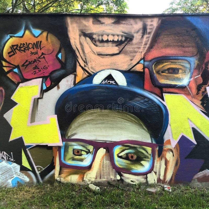 WROCŁAWSKI, POLAND-AUGUST 30, 2016: Kolorowy graffiti w tylnej alei śródmieście, przedstawia twarze ludzkie ilustracji