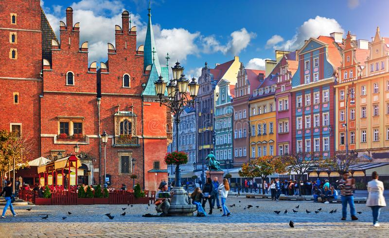 Wroclaw central market square with old colourful. Houses, street lamp and walking tourists people at evening sunset sunshine stock photos